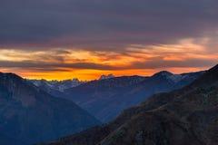 Luce solare variopinta dietro i picchi di montagna maestosi dell'italiano - alpi francesi, osservati da distante Nebbia e foschia Fotografia Stock