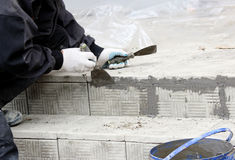 lucentezze del piastrellista sopra le lacune fra le mattonelle di pietra impilate sui punti nella riparazione dell'edificio per u Immagini Stock