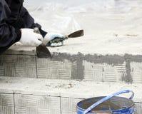 lucentezze del piastrellista sopra le lacune fra le mattonelle di pietra impilate sui punti nella riparazione dell'edificio per u Fotografie Stock Libere da Diritti