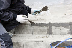lucentezze del piastrellista sopra le lacune fra le mattonelle di pietra impilate sui punti nella riparazione dell'edificio per u Immagine Stock Libera da Diritti