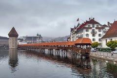LUCERNA, SUÍÇA - 28 DE OUTUBRO DE 2015: ponte nevoenta da manhã e da capela sobre o rio de Reuss, lucerna Imagem de Stock Royalty Free