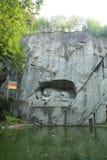 Lucerna, Svizzera - 30,2017 augusti: Bella statua della pietra del leone accanto al lago verde fotografia stock libera da diritti