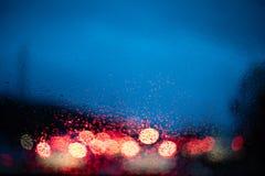 Luces borrosas de los coches por dentro de un coche con descensos en la ventana imagen de archivo
