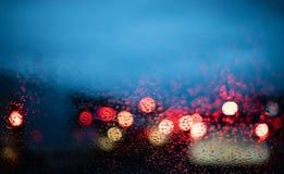 Luces borrosas de los coches por dentro de un coche con descensos en la ventana fotos de archivo