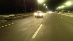 Luces brillantes estupendas en la calle, una conducción de automóviles y el conductor femenino, mostrando el dedo medio, 4k almacen de video