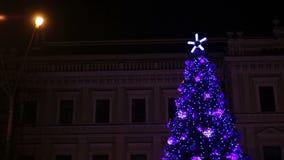 Luces brillantes que chispean en árbol fantástico del Año Nuevo en cuadrado central de la ciudad grande almacen de metraje de vídeo