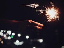 Luces de Bengala festivas, brillantes, ardientes en la mano del ` s del hombre imagen de archivo libre de regalías