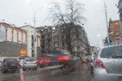 Luces de Bokeh de la calle desenfocado Autumn Abstract Backdrop Visión a través de la ventanilla del coche con gotas de lluvia Foto de archivo libre de regalías