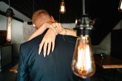 Luces de bulbos retras los recienes casados juntan el abarcamiento Imagen de archivo