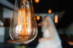Luces de bulbos retras los recienes casados juntan el abarcamiento Foto de archivo libre de regalías