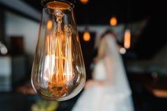 Luces de bulbos retras los recienes casados juntan el abarcamiento Fotografía de archivo libre de regalías