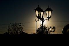 Luces de calle de la noche en el fondo de una luna muy brillante con los esquemas de árboles fotos de archivo libres de regalías