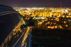 Luces de la ciudad reflejadas en coche Fotos de archivo