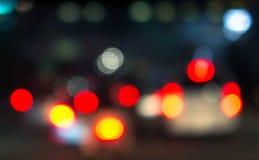 Luces de la cola del coche de Defocus en la noche Imagenes de archivo