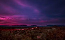 Luces de la cola a través del piso del desierto Fotografía de archivo libre de regalías