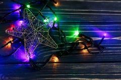 Luces de la guirnalda de la Navidad y estrella de oro en rústico negro elegante Imagenes de archivo