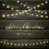 Luces de la Navidad coloridas en fondo de madera negro Fotografía de archivo