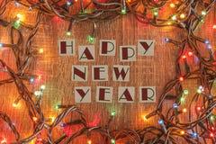 Luces de la Navidad con el texto de la Feliz Año Nuevo Imagen de archivo libre de regalías