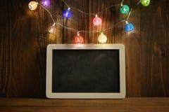 Luces de la Navidad con la pizarra de la pizarra Imagenes de archivo
