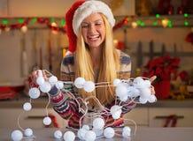 Luces de la Navidad de desenredo de la muchacha del adolescente Imágenes de archivo libres de regalías