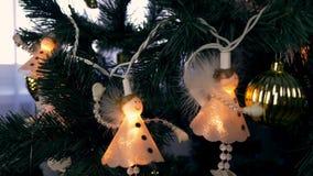 Luces de la Navidad en árbol de abeto Abeto verde con las luces blancas de ángeles Hange de los ángeles en ramas de árbol de navi almacen de metraje de vídeo