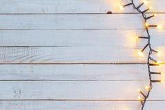 Luces de la Navidad en el fondo de madera blanco imagen de archivo libre de regalías