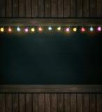 Luces de la Navidad en la pizarra de madera fotografía de archivo libre de regalías