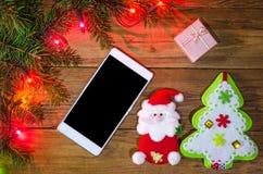 Luces de la Navidad en un fondo y un smartphone de madera, visión superior Foto de archivo