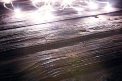 Luces de la Navidad de la falta de definición en tablones de madera Concepto de la Navidad o del Año Nuevo Imagenes de archivo