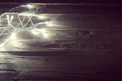 Luces de la Navidad de la falta de definición en tablones de madera Concepto de la Navidad o del Año Nuevo Imagen entonada Imágenes de archivo libres de regalías