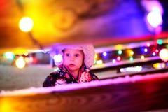 Luces de la Navidad de mirada exteriores del pequeño bebé en foto de archivo libre de regalías