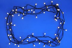 Luces de la Navidad que brillan intensamente en fondo del color fotografía de archivo libre de regalías