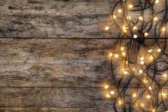 Luces de la Navidad que brillan intensamente en fondo de madera fotografía de archivo libre de regalías