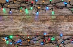 Luces de la Navidad que brillan intensamente en fondo de madera imagenes de archivo