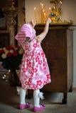 Luces de la niña a la vela en la iglesia Día de fiesta de Pascua fotos de archivo