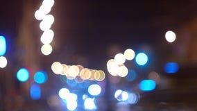Luces de la noche de la ciudad del centelleo a través de ramas metrajes