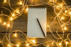 Luces de la nota y de la Navidad del papel en blanco en fondo de madera del vintage imagen de archivo libre de regalías