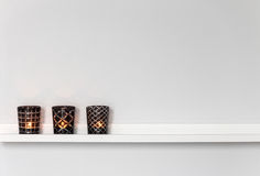 Luces de la vela en el estante blanco foto de archivo libre de regalías