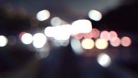 Luces de los coches y movimiento Defocused del fondo Los coches con las luces se encienden a través de la ciudad en la noche Real metrajes