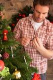 Luces del árbol de navidad de la fijación del hombre joven Fotos de archivo libres de regalías