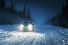 Luces del coche en bosque del invierno Imágenes de archivo libres de regalías
