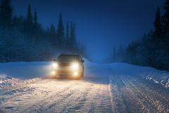 Luces del coche en bosque del invierno fotos de archivo libres de regalías