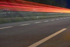 Luces del coche en el camino en la noche Imagen de archivo libre de regalías