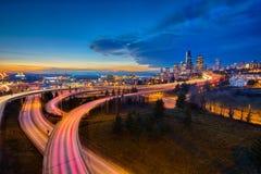Luces del coche que se arrastran y el horizonte de Seattle en la puesta del sol Foto de archivo