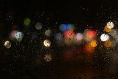 Luces del color en el vidrio de la ventana oscuro lluvioso imagenes de archivo