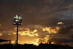 Luces del estadio encendidas y puesta del sol Fotos de archivo libres de regalías