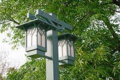 Luces duales al aire libre del estilo de la linterna en un poste del metal debajo de un árbol en un parque fotos de archivo