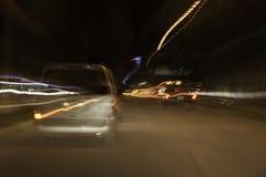Luces en el camino, coche que se mueve en la exposición larga Imagenes de archivo