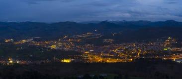 Luces en la noche en la ciudad de Renteria entre las montañas Imagen de archivo libre de regalías