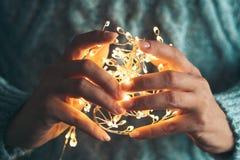 Luces en las palmas Las manos de las mujeres que sostienen una guirnalda Muchacha en un suéter azul con las luces de la Navidad e fotos de archivo libres de regalías